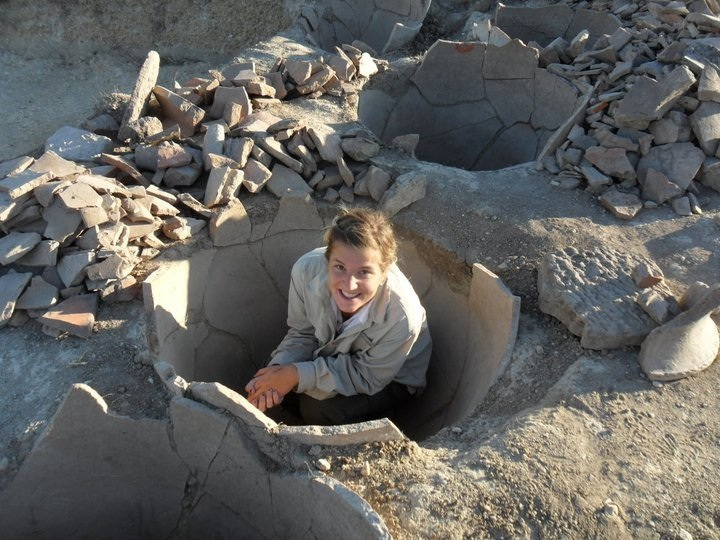Elizabeth demonstrates the size of a pithos (storage pot) at ancient Bylazora
