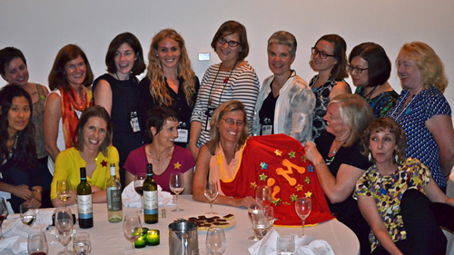 Williams is given the Mentoring Award and a superhero cape at the SWS banquet at ASA, surrounded by students and colleagues.