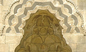A detail of the Portal of al-Zahir, Mashhad al-Husayn, featured on the cover of Mulder's book.