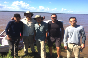 The large rivers team standing on the bank of the Amazon River after the acoustic Doppler and side-scan cross-sectional survey.