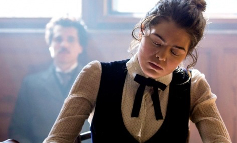 Actress Samantha Colley portrays Mileva Marić busily working on science, while the young Einstein lurks in the background.