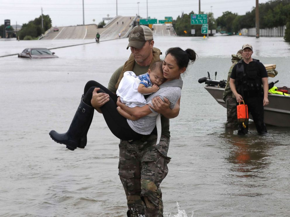 Houston Police SWAT officer Daryl Hudeck carries carries civilians from their home , Aug. 27, 2017, in Houston.