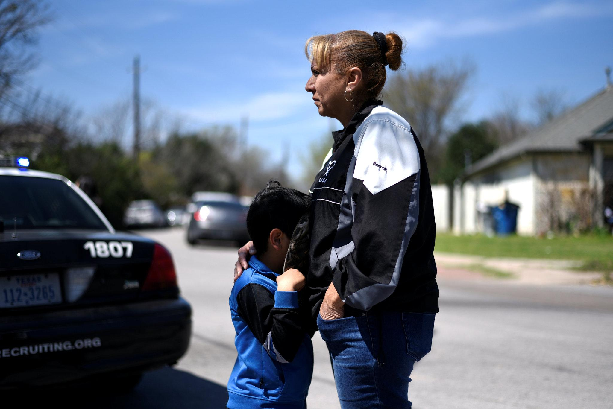 Isaac Machado and his mother, Delores, stand near the scene of a package bomb explosion in Austin, TX, on March 12. Credit: Sergio Flores/Reuters