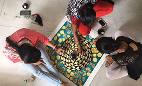Three artisans work together on a painting. Photo courtesy of Madhubani Art Center, Director Manisha Jha, New Delhi.