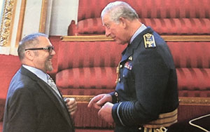 Prof. Emeritus Ian Hancock receiving a medal from Prince Charles