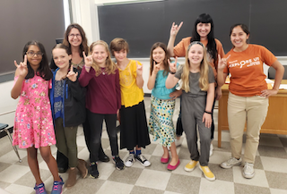 : Melissa Murphy and Heritage Track student Cynthia Lopez pose with students from the 3rd-5th grade group and their instructor.