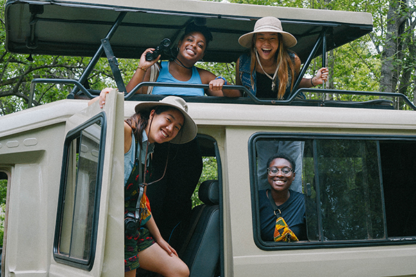 Four smiling female students stand in a safari truck smiling at the camera.