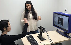 Lupita (standing) working in the eye-tracking lab with Research Assistant Italia Lopez-Valenzuela